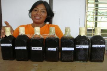 Staff showing the organic liquid fertilizer.